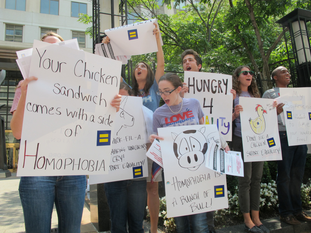Protesters hold signs and shout slogans outside a Chick-fil-A food truck in a mid-day demonstration organized by the Human Rights Campaign in Washington on 26 July, 2012 after the fast-food firm's president Dan Cathy came out against marriage equality in the United States. The protesters accused Chick-fil-A of a long history of supporting groups that 'demonize' gay and lesbian people. Cathy told a Christian news journal that Americans have invited God's judgement by accepting same-sex marriage.