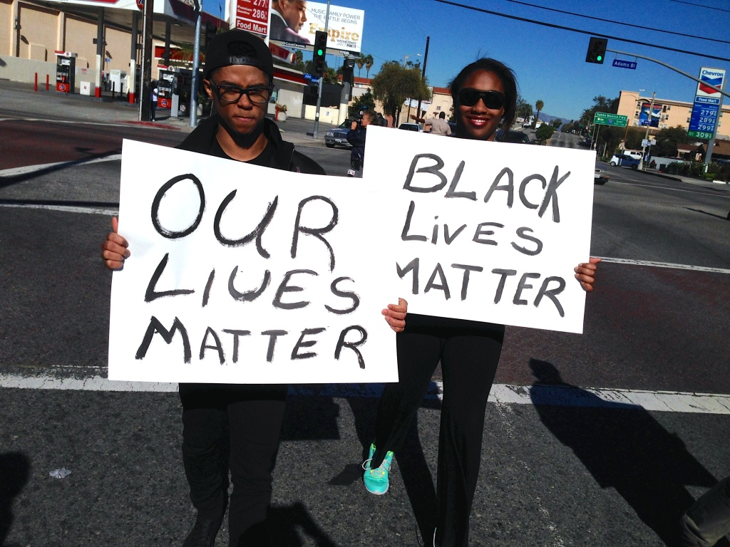 Friends LaVonce Goodlow, 19, and Priscilla Perry, 21, march down Crenshaw Boulevard to Leimert Park as part of an annual Kwanzaa celebration.
