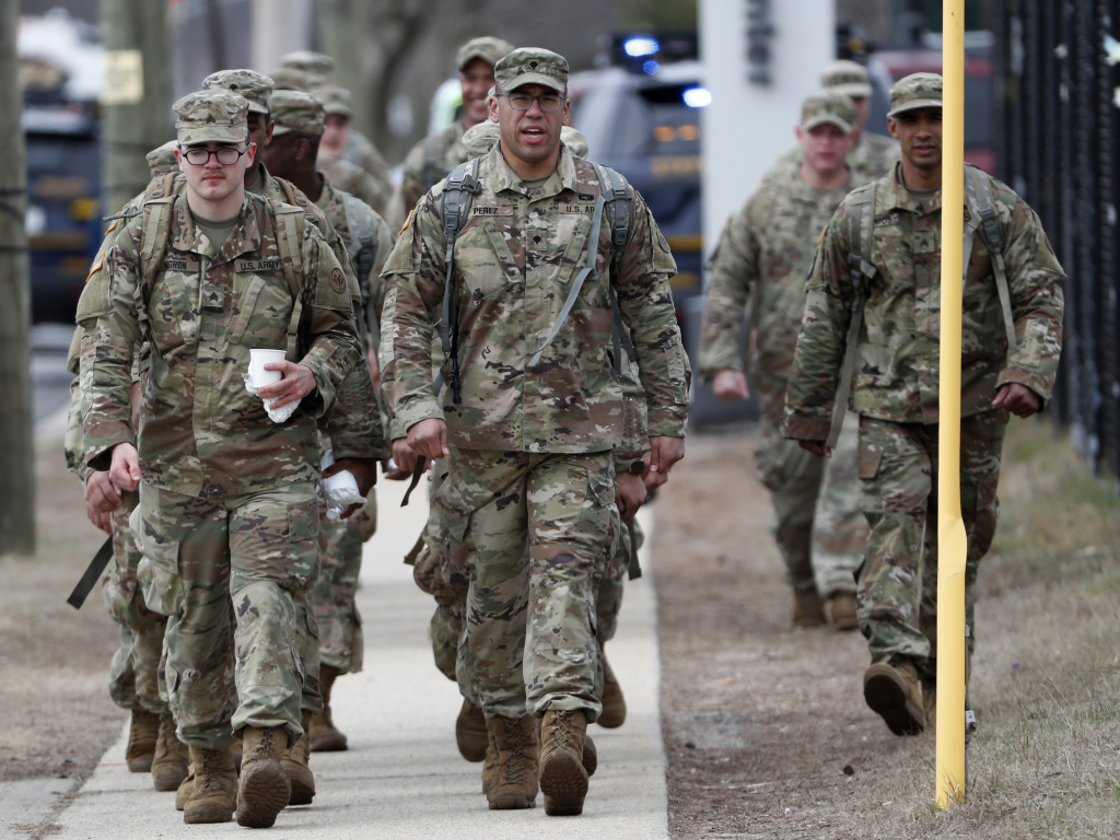 National Guard personnel march in formation Thursday at a state-managed coronavirus drive-through testing site that just opened on Staten Island in New York.
