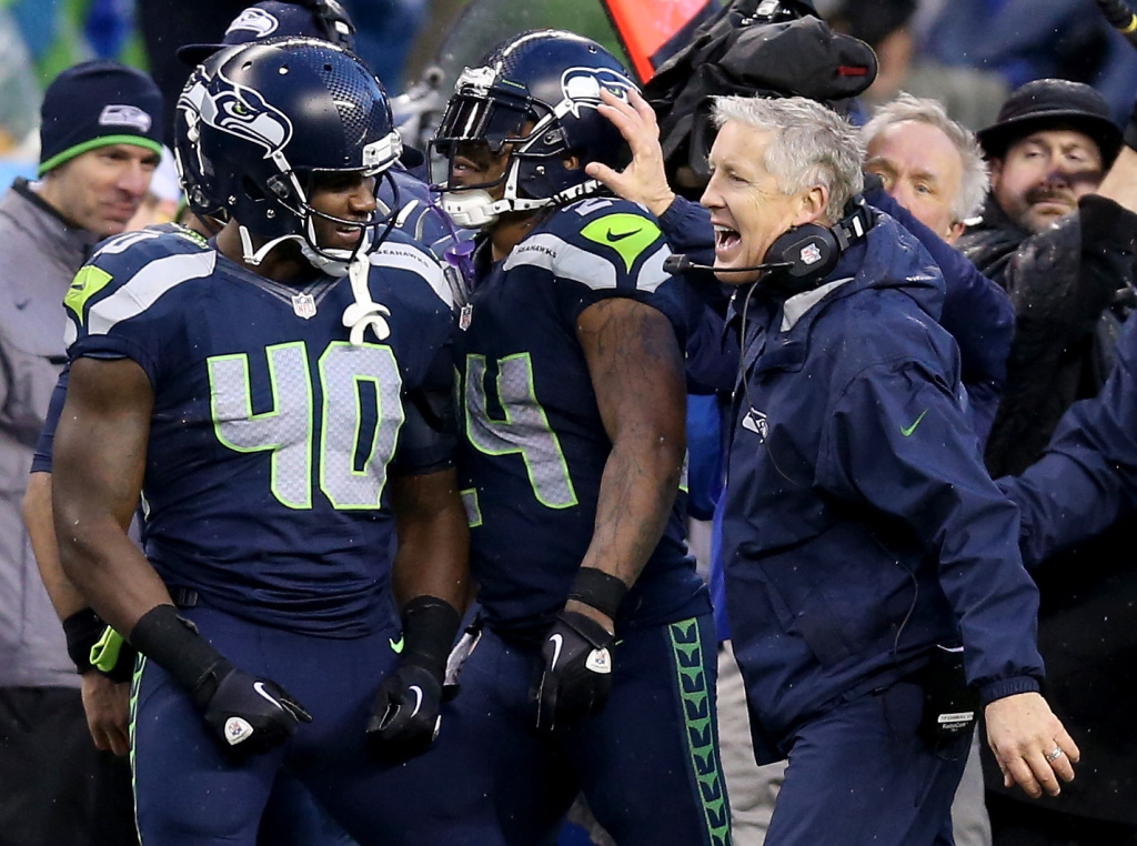 Head coach Pete Carroll of the Seattle Seahawks celebrates with running back Marshawn Lynch #24 after Lynch scores a touchdown in the fourth quarter against the New Orleans Saints in the NFC Divisional Playoff Game at CenturyLink Field on January 11, 2014 in Seattle, Washington.