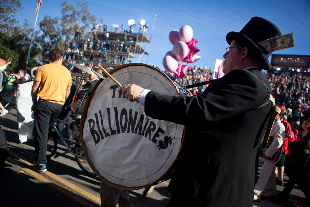 An Occupy protester dressed as a billionaire rounds the corner in front of the media scaffolding on the Rose Parade route.