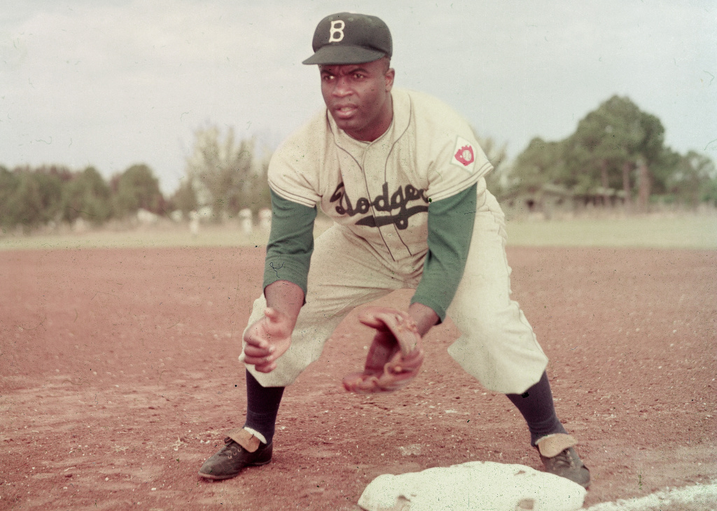 American professional baseball player Jackie Robinson (1919 - 1972) of the Brooklyn Dodgers, dressed in a road uniform, crouches by the base and prepares to catch a ball, 1951. Throughout the course of his baseball career Robinson played several positions on the infield as well as serving as outfielder.