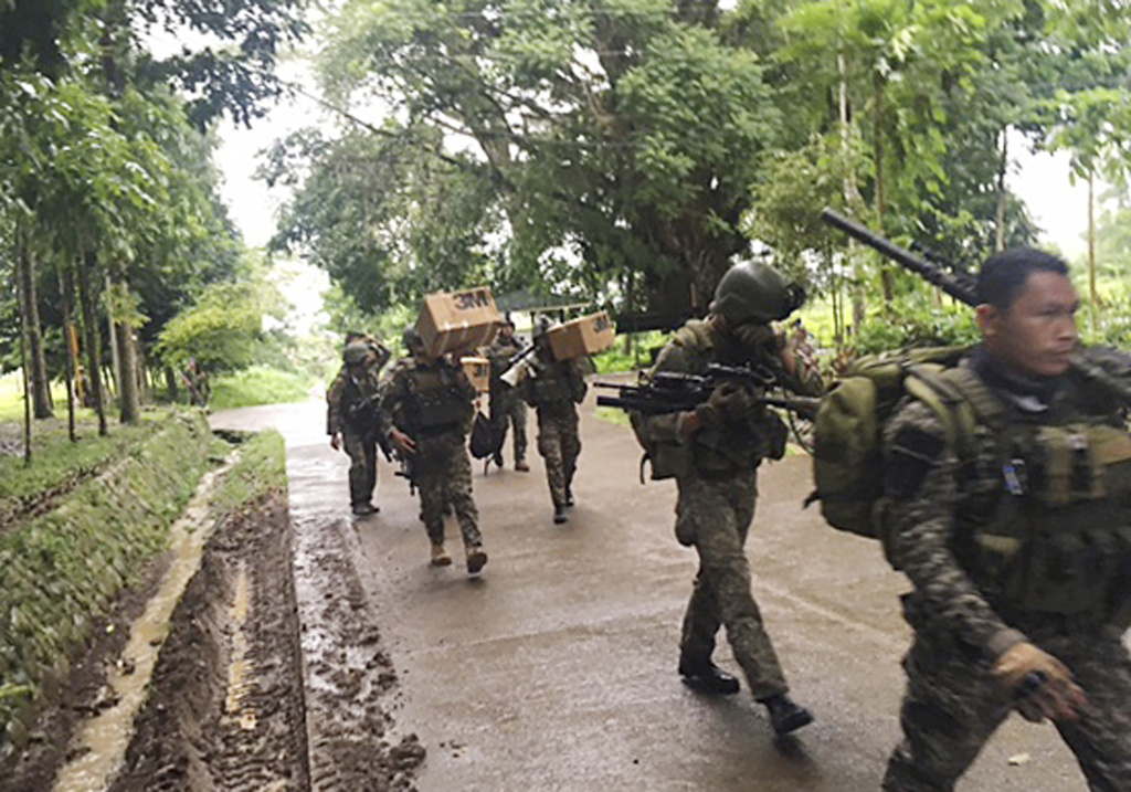 Philippine troops arrive at their barracks to reinforce fellow troops following the siege by Muslim militants Wednesday, May 24, 2017 in the outskirts of Marawi city in southern Philippines. Muslim extremists abducted a Catholic priest and more than a dozen churchgoers while laying siege to a southern Philippine city overnight, burning buildings, ambushing soldiers and hoisting flags of the Islamic State group, officials said Wednesday. President Rodrigo Duterte declared martial law in the southern third of the nation and warned he would enforce it harshly. (AP Photo)