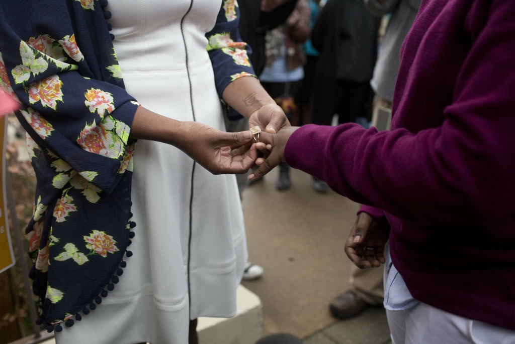 Tori Sisson, left, and Shante Wolfe, right, exchange wedding rings during their wedding ceremony, Monday, Feb. 9, 2015, in Montgomery, Ala. Sisson and Wolfe were the first couple to file their marriage license in Montgomery County.