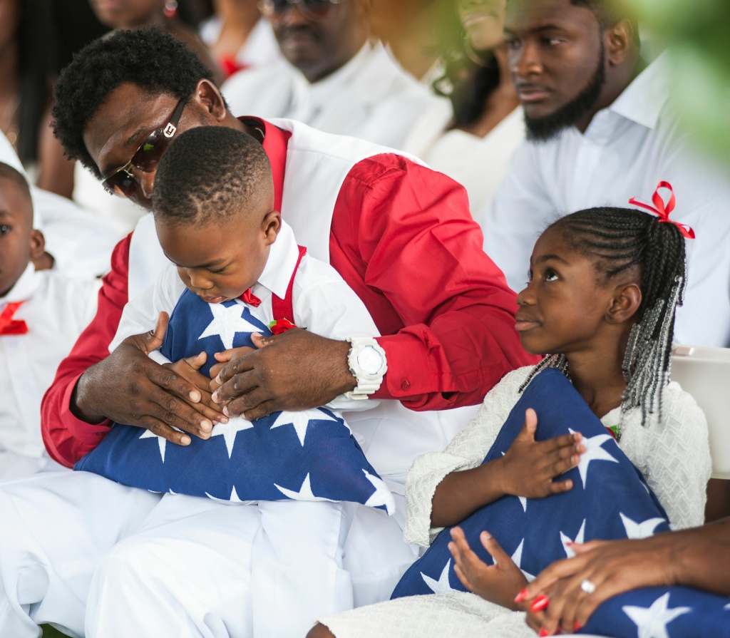 Richard Johnson, Sr., holds the hand of La David Johnson Jr., as he and sister Ah'Leesya Johnson hold folded U.S. flags given to them during the burial service for their father, U.S. Army Sgt. La David Johnson on October 21, 2017 in Hollywood, Florida.