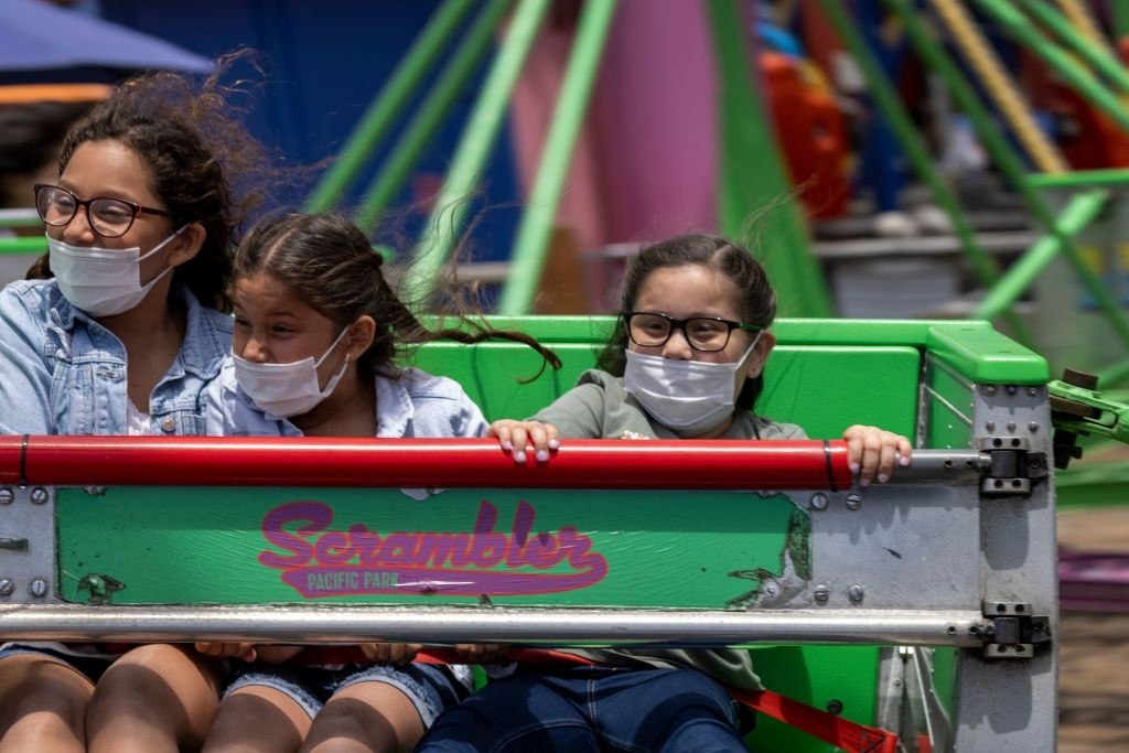 People spins on a ride at Pacific Park amusement park on the Santa Monica Pier as crowds gather on Memorial Day as shutdowns are relaxed more than a year after Covid-19 pandemic shutdowns began, in Santa Monica, California on May 31, 2021.