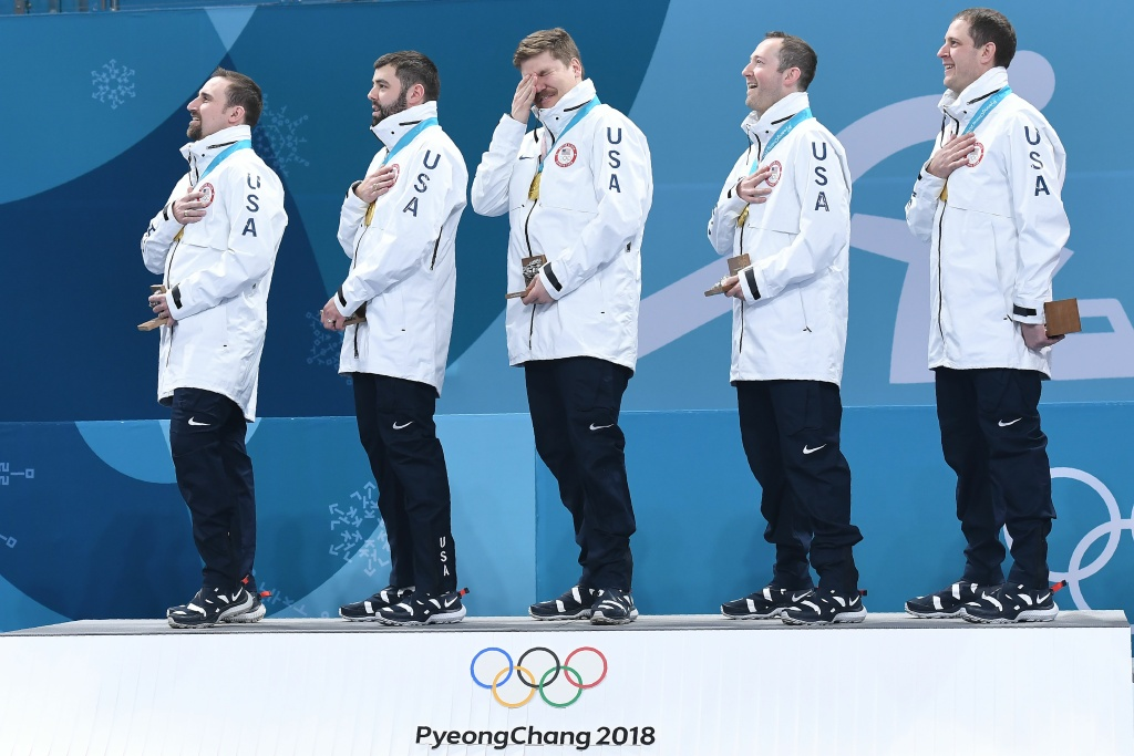 TOPSHOT - USA's Matt Hamilton (C) reacts as his team listens to their national anthem after winning curling men's gold medal game between the USA and Sweden during the Pyeongchang 2018 Winter Olympic Games at the Gangneung Curling Centre in Gangneung on February 24, 2018. / AFP PHOTO / WANG Zhao        (Photo credit should read WANG ZHAO/AFP/Getty Images)