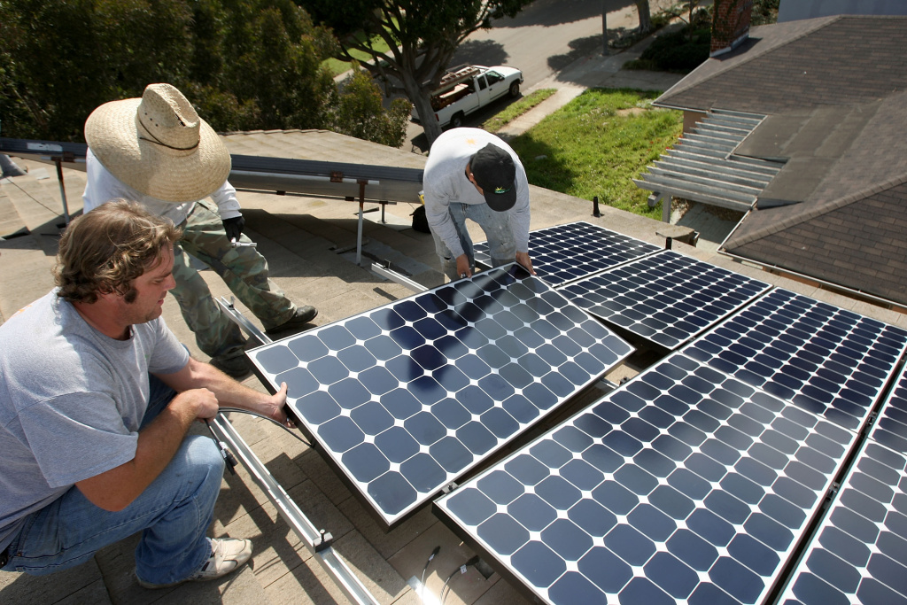 Workers install solar panels on a residential rooftop on February 27, 2009 in Santa Monica. Residential solar sales dipped in California in 2016 compared to 2015.