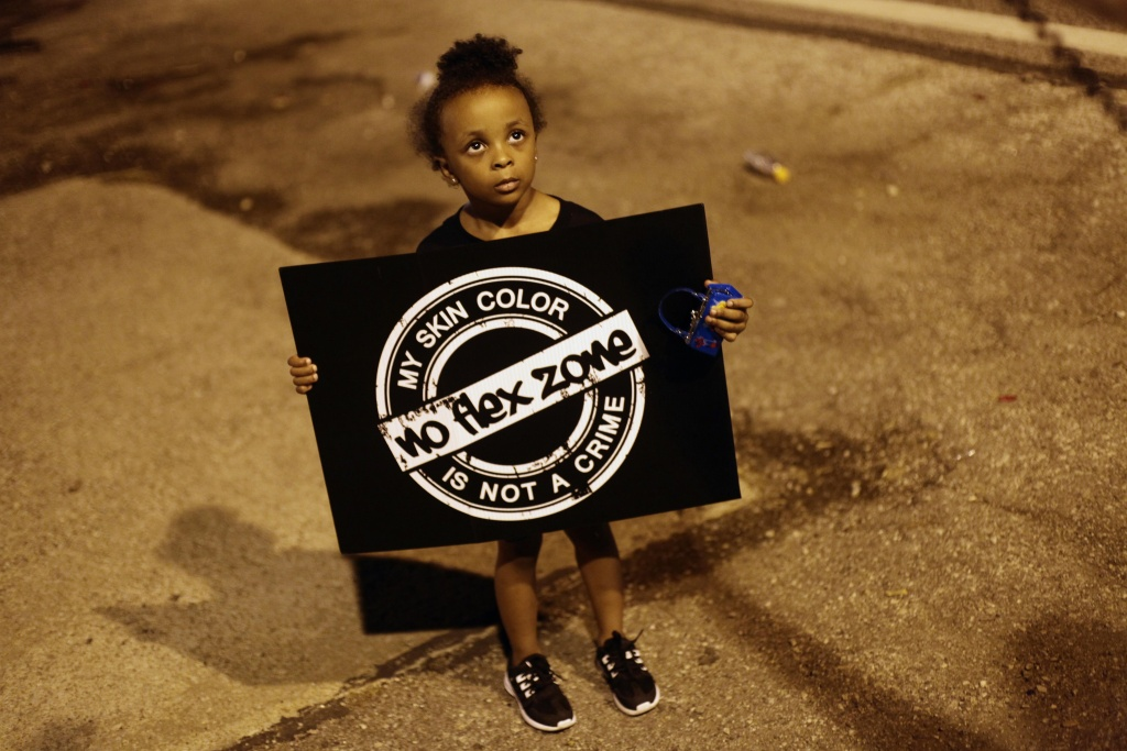 A girl holds a sign as she protests the shooting of Michael Brown August 21, 2014 in Ferguson, Missouri. Crowds continue to gather to march along Florissant Road after Brown was fatally shot by Ferguson Police Officer Darren Wilson August 9th.