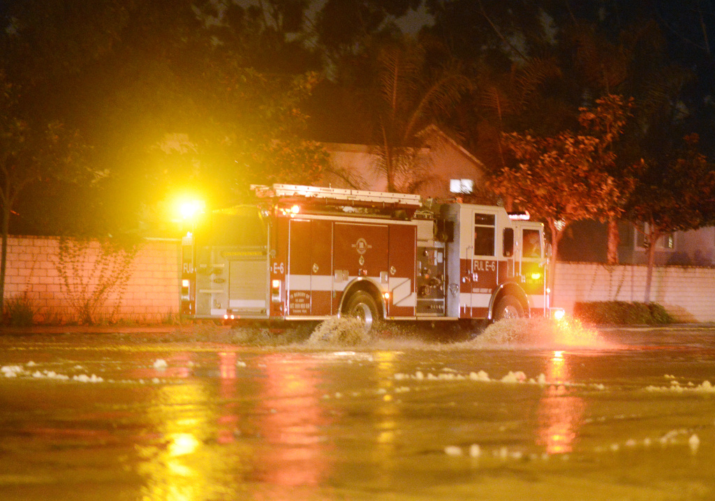 A Fullerton fire engine drives on flooded Gilbert Street in Fullerton after a 5.1 magnitude earthquake burst a water main Friday evening March 28, 2014.