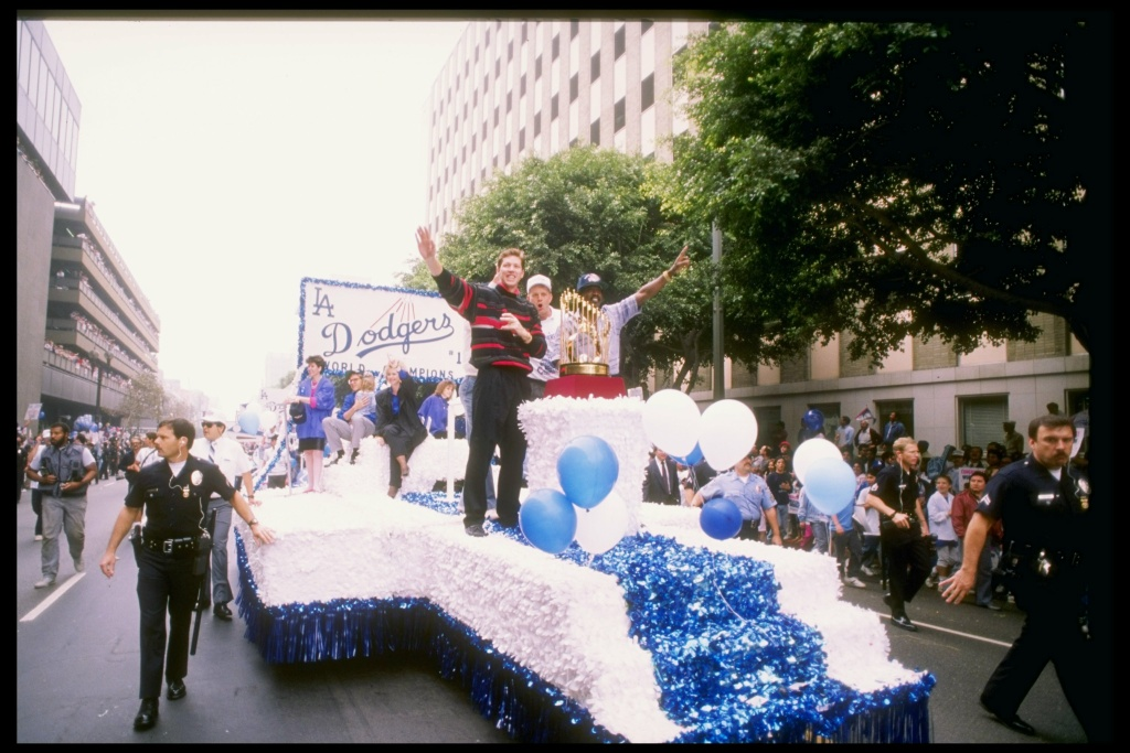 October 1988: Pitcher and World Series MVP Orel Hershiser #55 of the Los Angeles Dodgers waves to the crowd with the World Series Trophy next to him during the Dodgers' victory parade in Los Angeles, California.