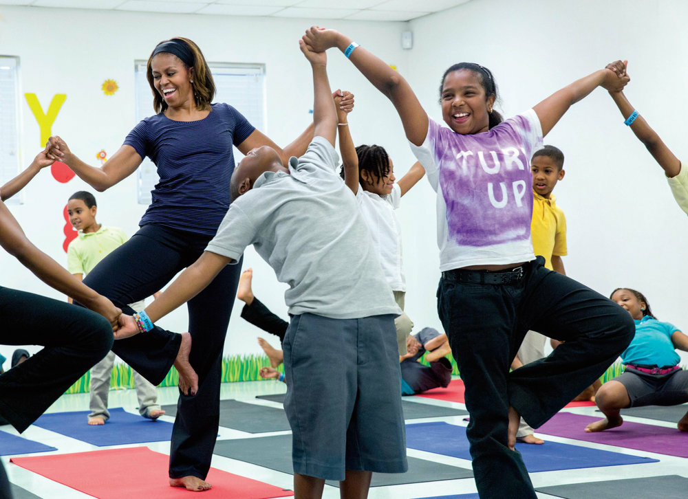 First Lady Michelle Obama joins children for a yoga class during a Let's Move! after-school activities event at Gwen Cherry Park in Miami, Florida, February 25, 2014.