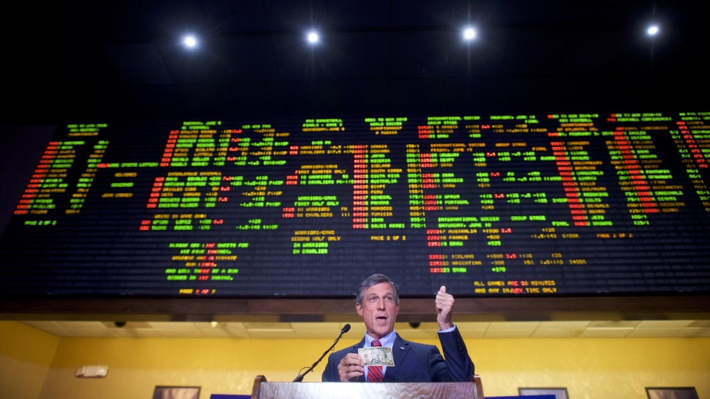 Delaware Gov. John Carney holds a $10 bill he used to place the first bet at Dover Downs Casino on June 5, in Dover, Del. Delaware is the first state to launch legal sports betting since a Supreme Court decision allowed states to legalize such gambling.