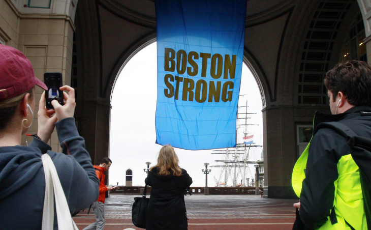 People photograph a banner reading