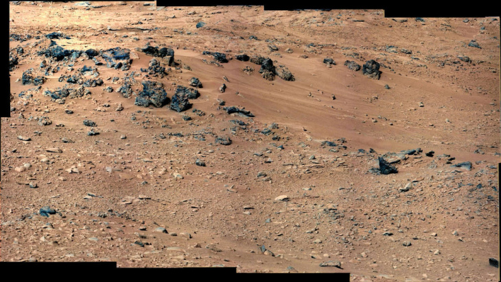 This patch of windblown sand and dust downhill from a cluster of dark rocks is the