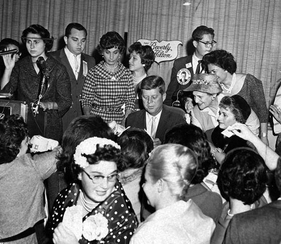 "June 8, 1963: Women's Division of the Democratic State Central Committee of California holds $10-a-plate breakfast for Kennedy. Original caption reads, ""He arrives at Palladium to the cheering of more than 3000 women."" City Councilmember Rosalind Wyman, n"