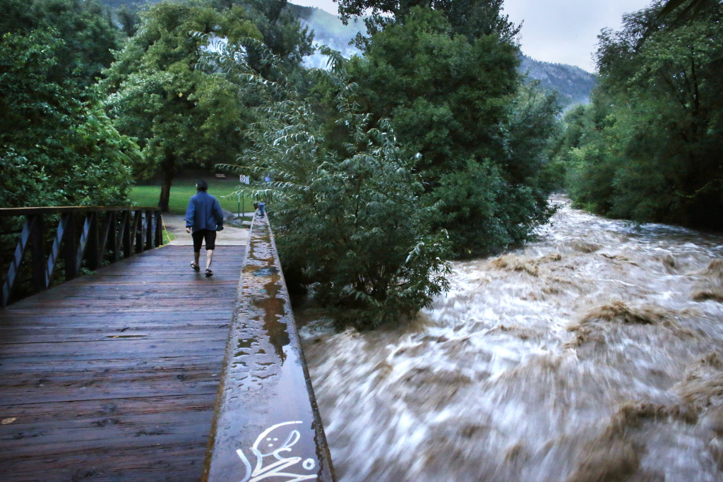 During a break in the rain, a woman walks over a footbridge past Boulder Creek which roils at high speed after days of record rain and flooding, at the base of Boulder Canyon, Colo., Friday Sept. 13, 2013.  People in Boulder were ordered to evacuate as water rose to dangerous levels amid a storm system that has been dropping rain for a week. Rescuers struggled to reach dozens of people cut off by flooding in mountain communities, while residents in the Denver area and other areas were warned to stay off flooded streets. (AP Photo/Brennan Linsley)