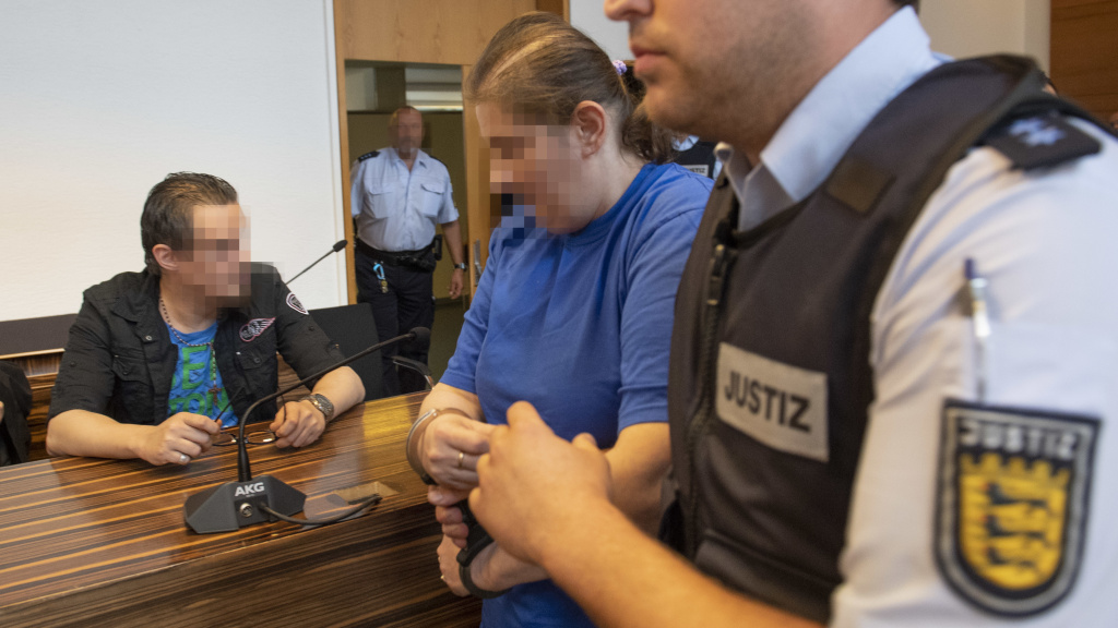 The defendant identified as Berrin T. (right) is led past defendant Christian L. (left) ahead of their sentencing hearing Tuesday at the district court in Freiburg, Germany. Getty Images says their faces have been pixelated in accordance with court orders.