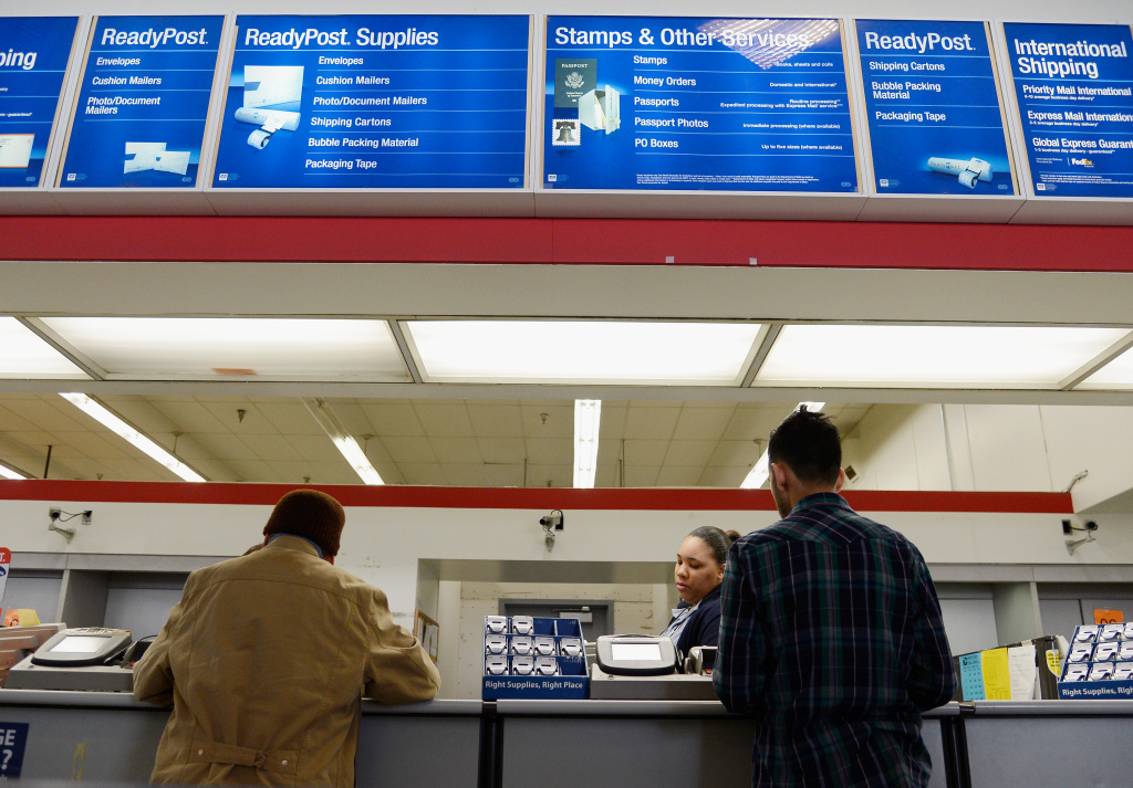 A U.S. Postal Service clerk helps customers at the Los Feliz Post Office.