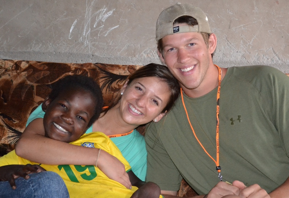 Clayton and Ellen Kershaw in Africa with one of the orphans they've come to know through their work with Arise Africa.