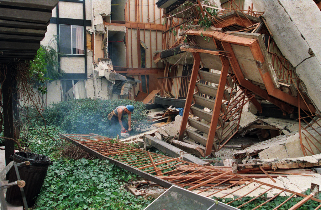 A construction worker using a chain on January 24, 1994, starts to cut up some of the destroyed walls in the courtyard of Northridge Meadow, the apartment complex that collapsed during the Northridge earthquake. Sixteen people were killed when the building collapsed during the quake. Councilman Tom LaBonge is now proposing an inventory of so-called