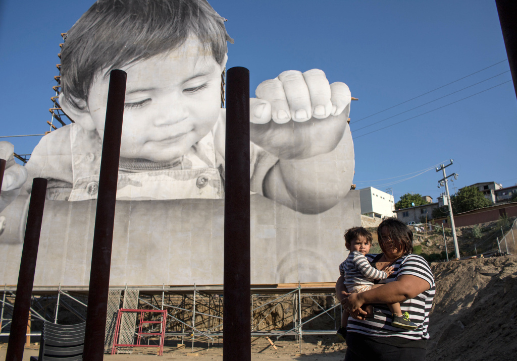 Lissy and her son Enrique Achondo, who was pictured by French artist JR for his artwork, poses for a picture on the Mexican side of the US - Mexico border where the giant print of Enrique has been installed in Tecate, Baja California, Mexico on September 6, 2017.