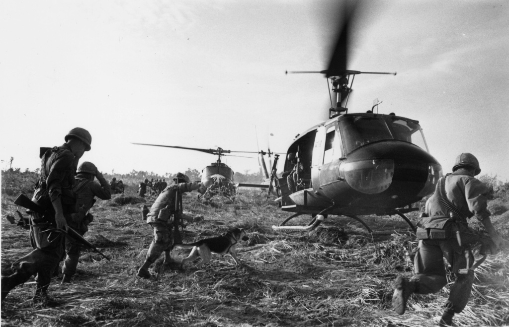 US Marines running towards a Bell (UH 1) Huey helicopter and crew in the Tay Ninh area of Vietnam.