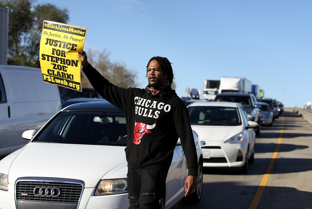 SACRAMENTO, CA - MARCH 22:  A Black Lives Matter protester holds a sign as he marches on Interstate 5 during a demonstration on March 22, 2018 in Sacramento, California.  Hundreds of protesters staged a demonstration against the Sacramento police department after two officers shot and killed Stephon Clark, an unarmed black man, in the backyard of his grandmother's house following a foot pursuit on Sunday evening.  (Photo by Justin Sullivan/Getty Images)