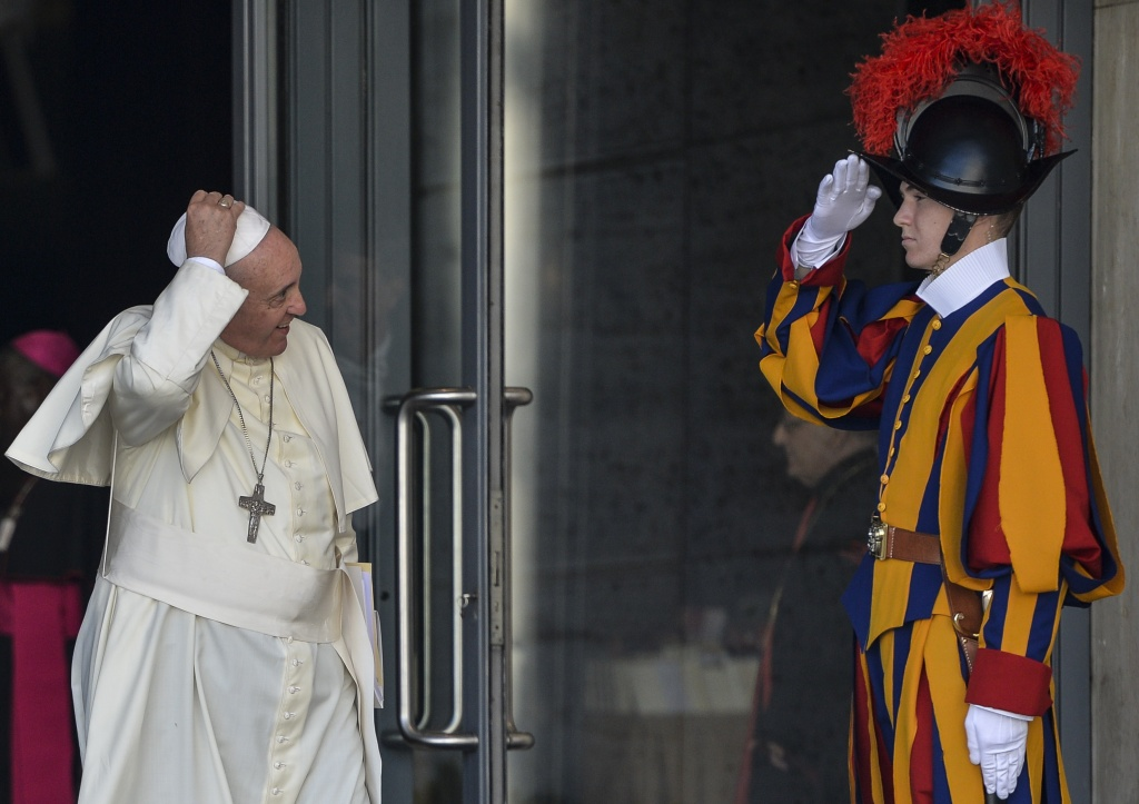 Pope Francis (C) holds his skullcup in front of a Swiss guard as he leaves at the end of the morning session of the Synod on the Families, at the Vatican, on October 6, 2014. Pontiff on Sunday launched a major review of Catholic teaching on the family that could lead to change in the Church's attitude to marriage, cohabitation and divorce. An extraordinary synod, or meeting, of nearly 200 bishops from around the world and a sprinkling of lay people will, for the next two weeks, address the huge gulf between what the Church currently says on these issues and what tens of millions of believers actually do.