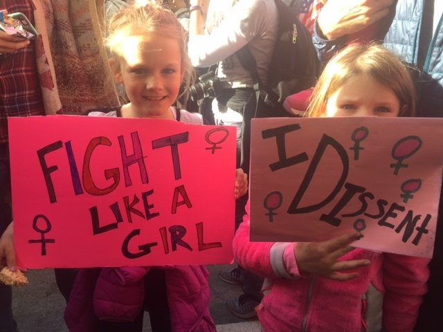 Attendees at the Women's March of Los Angeles hold signs in the streets of Downtown L.A.