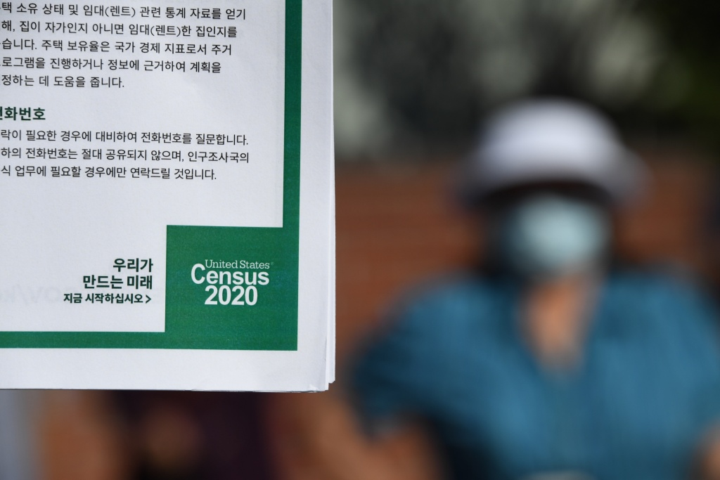 A volunteer displays information in Korean encouraging people to complete the US Census, at a food distribution bank for people facing economic hardship or food insecurity, in a church parking lot in Los Angeles, California, August 10, 2020 amid the COVID-19 pandemic.