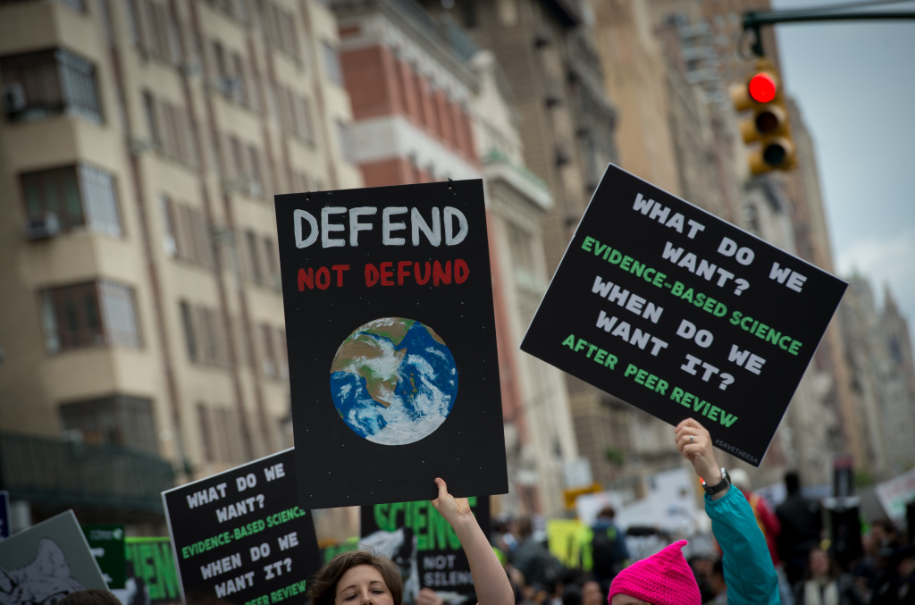 People hold up signs at a rally before the March for Science April 22, 2017 in New York.  Scientists and their supporters across the globe are expected to march in the thousands Saturday amid growing anxiety over what many see as a mounting political assault on facts and evidence. / AFP PHOTO / Bryan R. Smith        (Photo credit should read BRYAN R. SMITH/AFP/Getty Images)