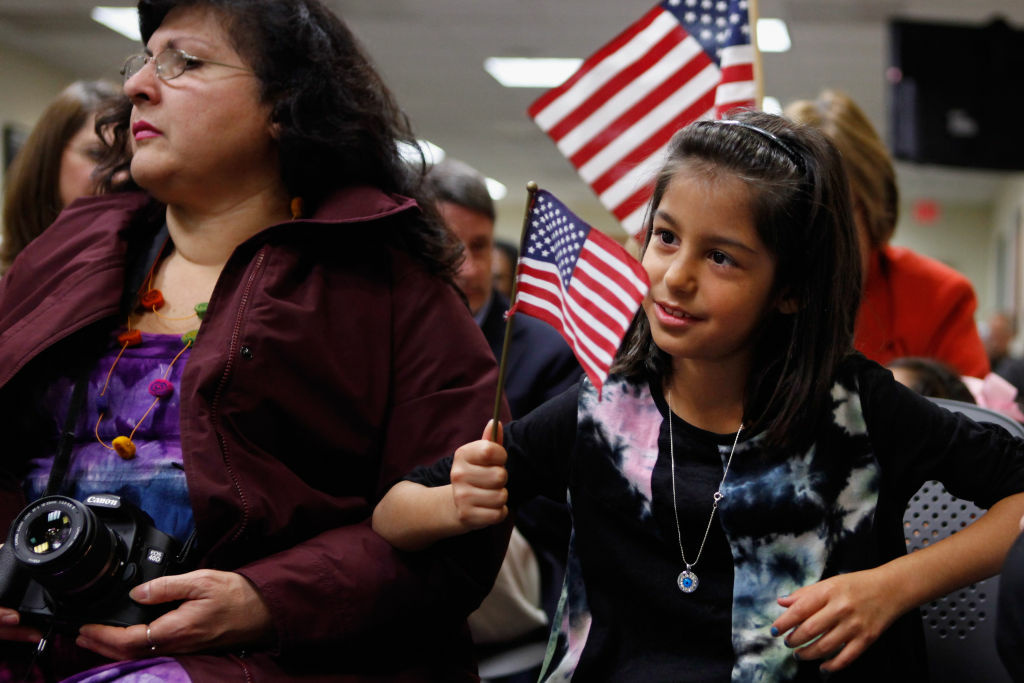 Born in Bulgaria, Stephanie Marinova (R), 7, sits with her adopted mother Beatrice Tolidjian of Annandale, VA, during the children's citizenship ceremony at the U.S. Citizenship and Immigration Services office November 14, 2011 in Fairfax, Virginia. In celebration of National Adoption Month, 25 children representing nine countries, including Bulgaria, China, Ethiopia, Guatemala, Korea, Liberia, Russia, Taiwan and Vietnam, celebrated their U.S. citizenship during the ceremony.