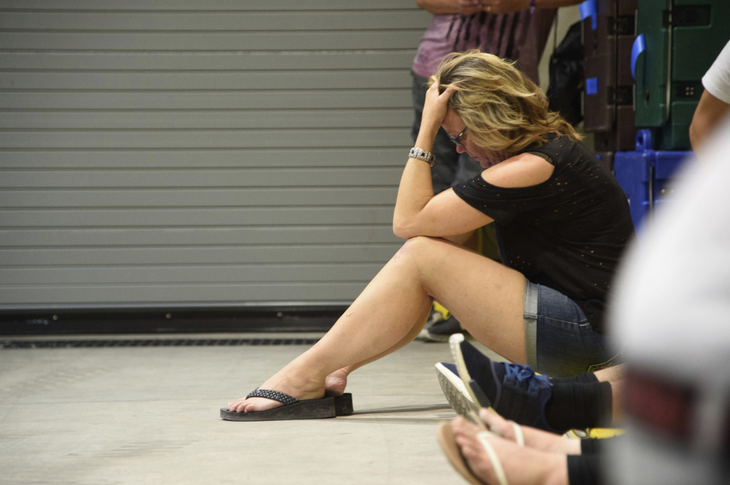 A young woman hides inside the Sands Corporation plane hangar after a gunman opened fire at the Route 91 Harvest Festival on Sunday, Oct. 1, 2017, in Las Vegas.