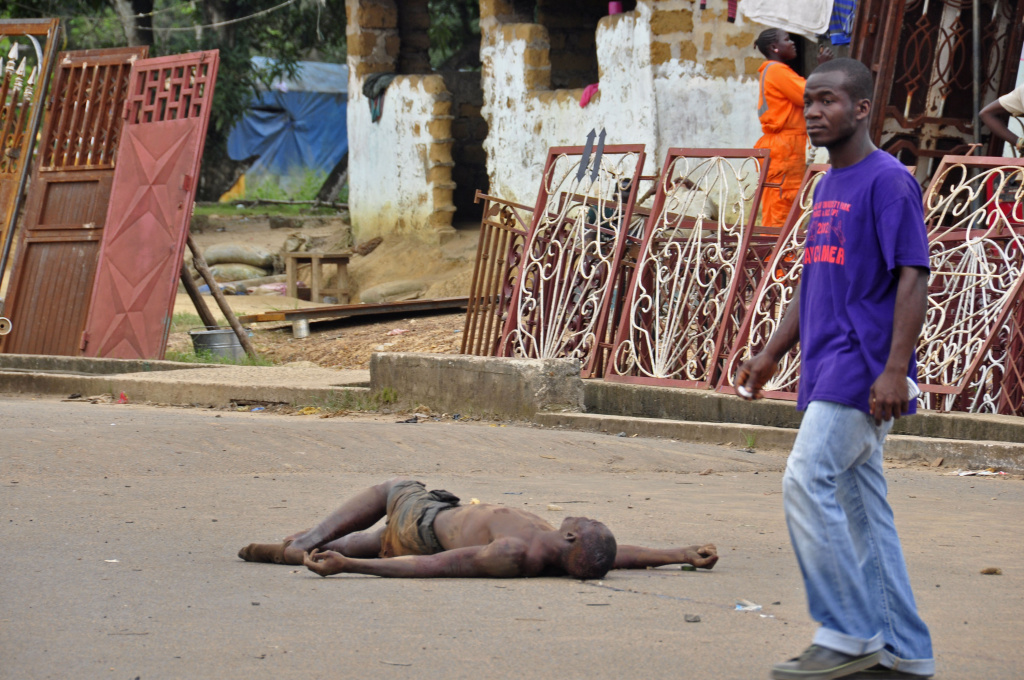 The lifeless body of a man lays unattended in the street as locals suspect him of dying from the deadly Ebola virus, as government warns the public not to leave Ebola victims in the streets in the city of Monrovia, Liberia, Tuesday,  Aug. 5, 2014.  A second American aid worker infected with Ebola arrived Tuesday in Atlanta, where doctors will closely monitor the effect of an experimental drug she agreed to take even though its safety was never tested on humans. Nancy Writebol arrived from Monrovia, Liberia, in a chartered plane at Dobbins Air Reserve Base and will join Dr. Kent Brantly in the isolation unit at Emory University Hospital, just downhill from the U.S. Centers for Disease Control and Prevention.