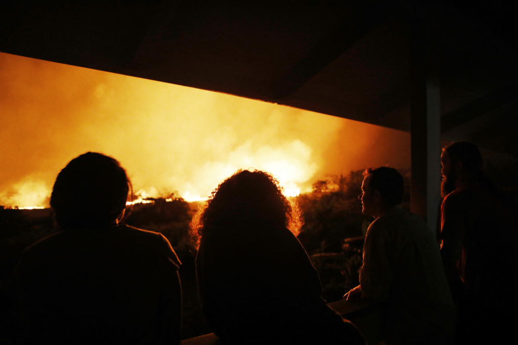 Residents view lava erupting from a Kilauea volcano fissure, at a small viewing party on a neighbor's porch, on Hawaii's Big Island on May 19, 2018 in Kapoho, Hawaii.