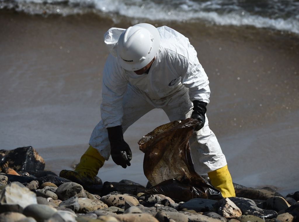 A worker cleans oil from the rocks and beach at Refugio State Beach in Goleta, California, May 22, 2015. The oil company behind a crude spill on the California coast vowed to do the