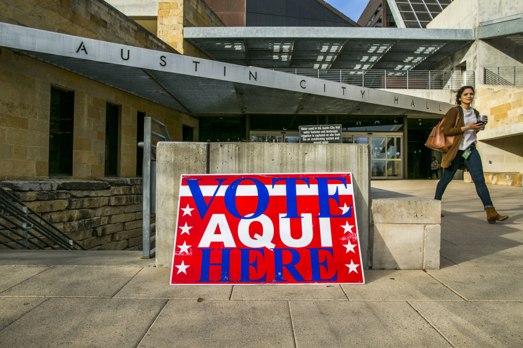 A pedestrian walks past Austin City Hall, an early voting center, in March. Texas was the first state to go to the polls to vote in midterm primaries.