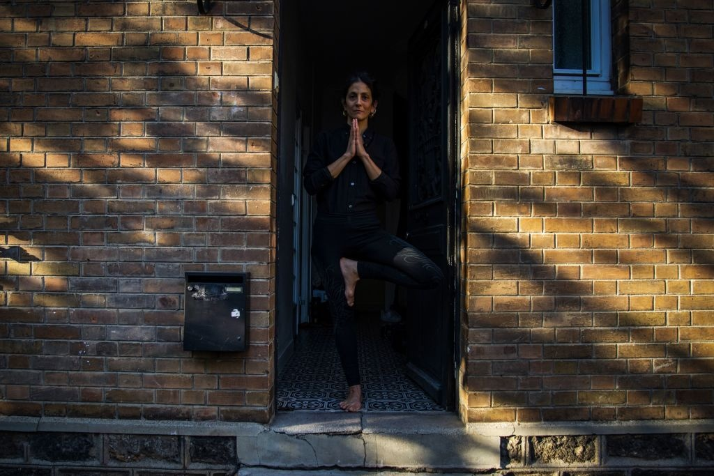 Maddalena, practises yoga at the entrance of her house, in Bagnolet, on the outskirts of Paris, on April 14, 2020, on the 29th day of a strict lockdown aimed at curbing the spread of the COVID-19 (the novel coronavirus).