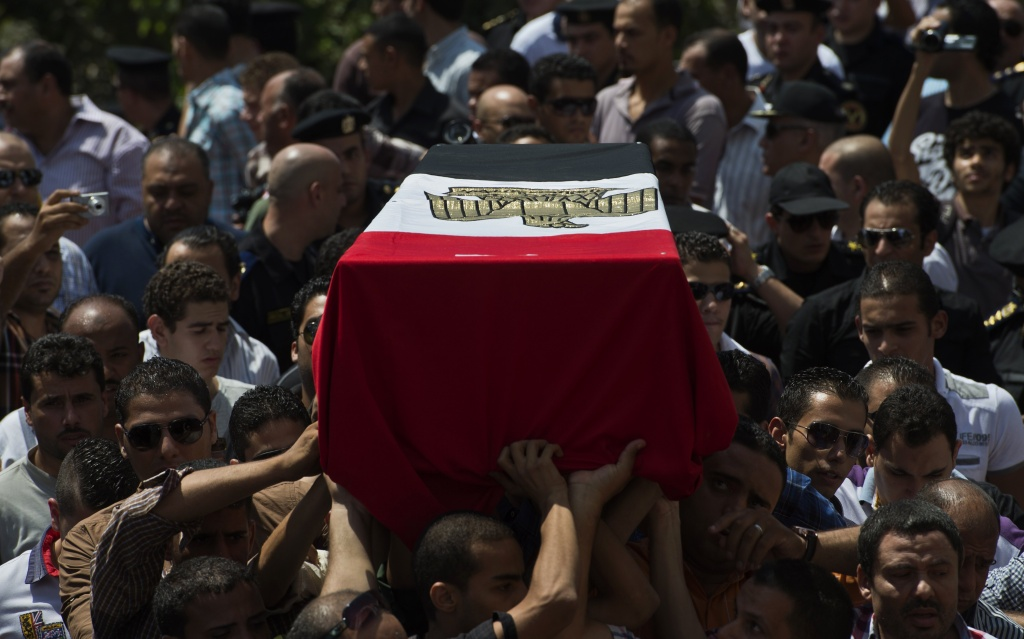 Egyptians carry the coffin of one of the four policemen, killed during clashes with Muslim Brotherhood supporters earlier in the week, during their funeral in Cairo on August 15, 2013.