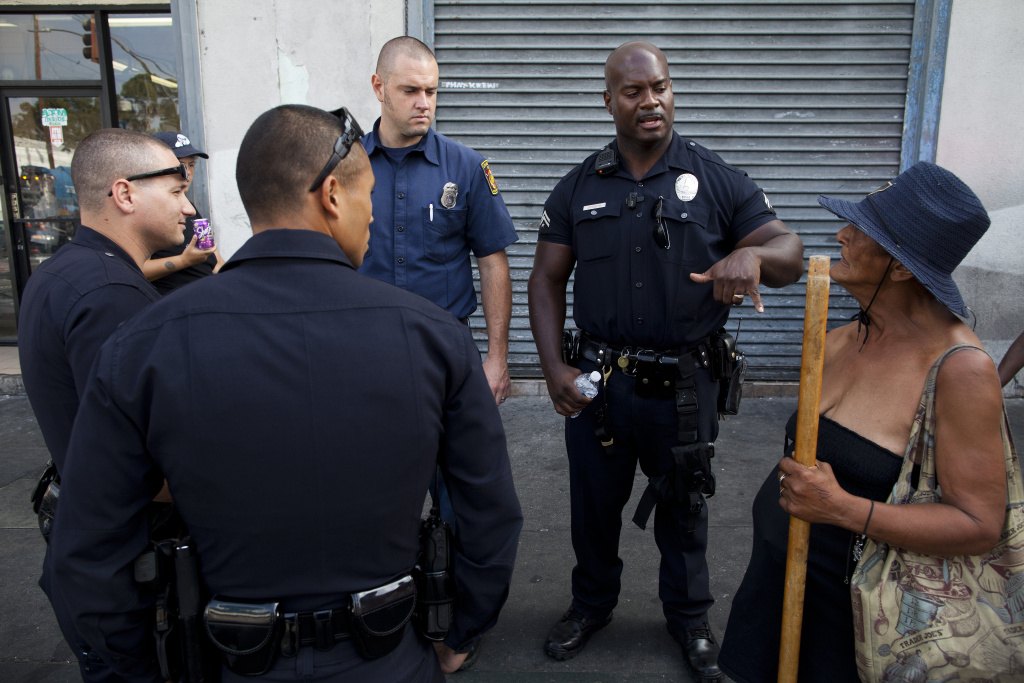 LAPD Officer Deon Joseph and other LAPD officers engage a woman who said she was robbed early in the day on Skid Row.