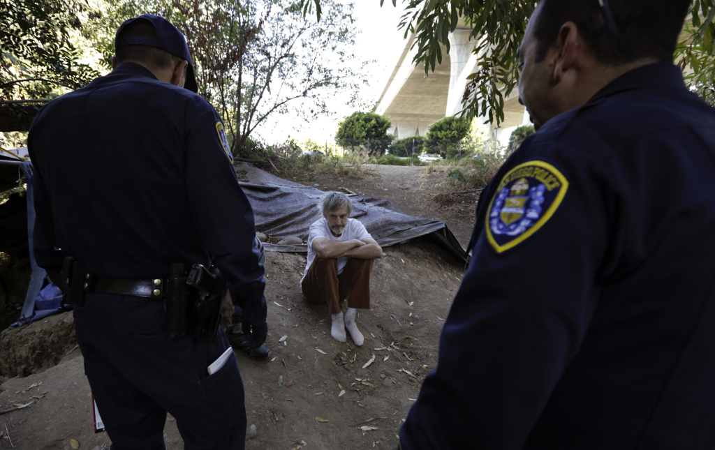 In this Sept. 28, 2017, photo, Stephen Schofield looks on as police officials encourage him to get a Hepatitis A vaccination near where is living along the San Diego River in San Diego. A recent Hepatitis A outbreak - the worst epidemic of its kind in 20 years in the United States - reflects how much homelessness has become a crisis in San Diego, a top tourist destination known for its sunny weather, surfing and fish tacos that bills itself as