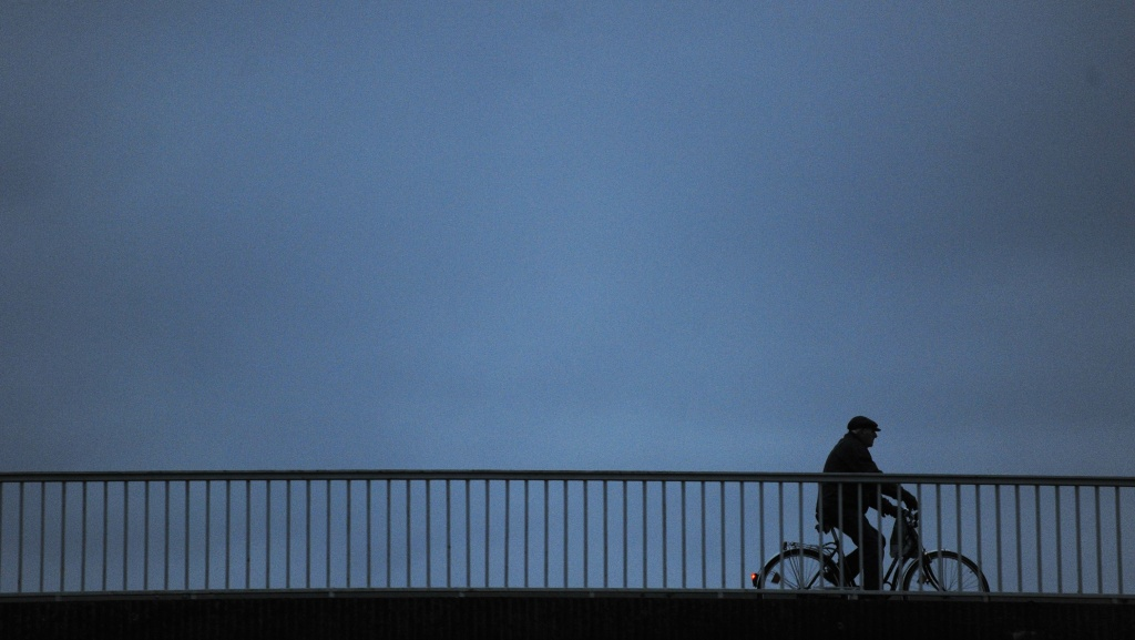 A commuter makes his way on a bicycle over a bridge during evening rush hour, Germany, 2010.