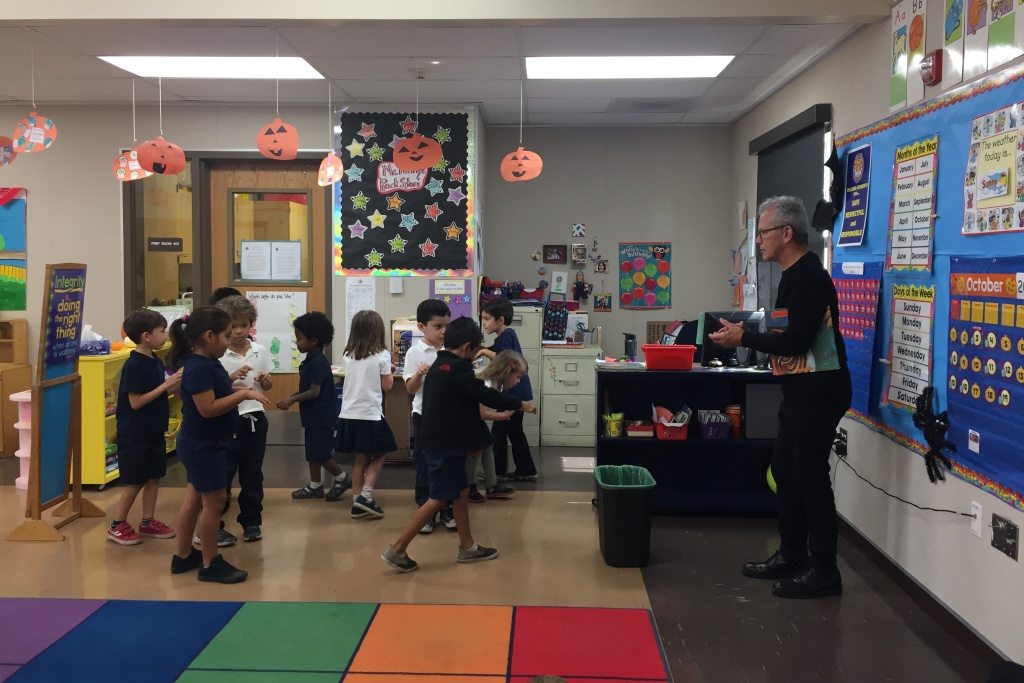 Music Center teaching artist Peter Kors instructs Willard Elementary students to move around a makeshift stage like tigers without running into each other. Kors says the activity teaches teamwork.