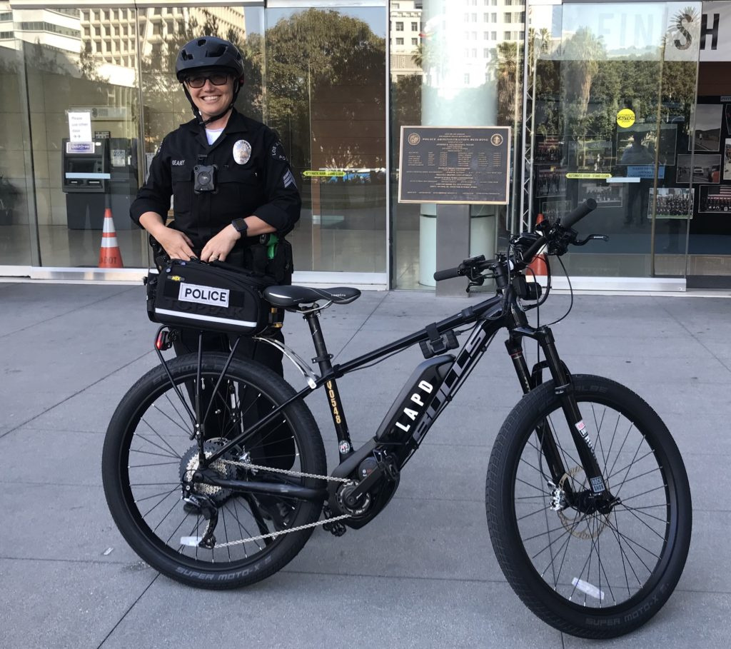 An LAPD officer stands with one of the new e-bikes in the department's fleet.