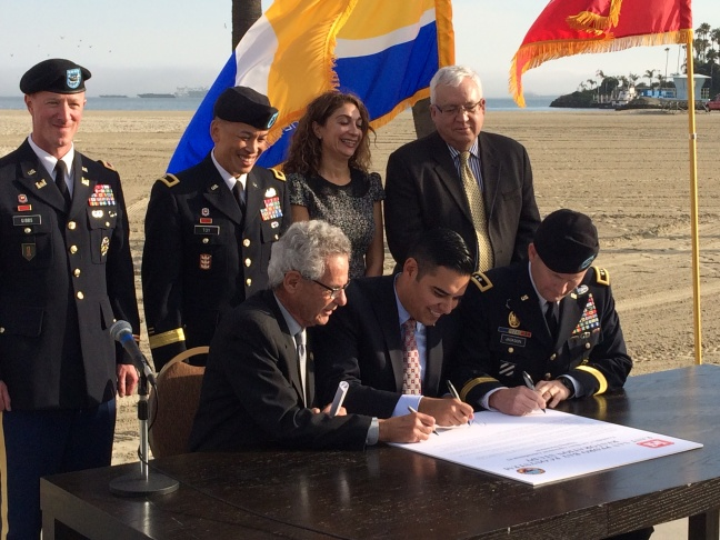 Long Beach Mayor Robert Garcia, center, signs the breakwater agreement with the U.S. Army Corps of Engineers.