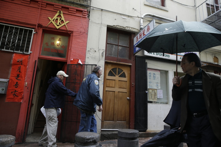 A man looks on as FBI and San Francisco police search a Chinatown fraternal organization, Wednesday, March 26, 2014, in San Francisco. California State Sen. Leland Yee was arrested Wednesday during a series of raids by the FBI in Sacramento and the San Francisco Bay Area, authorities said.
