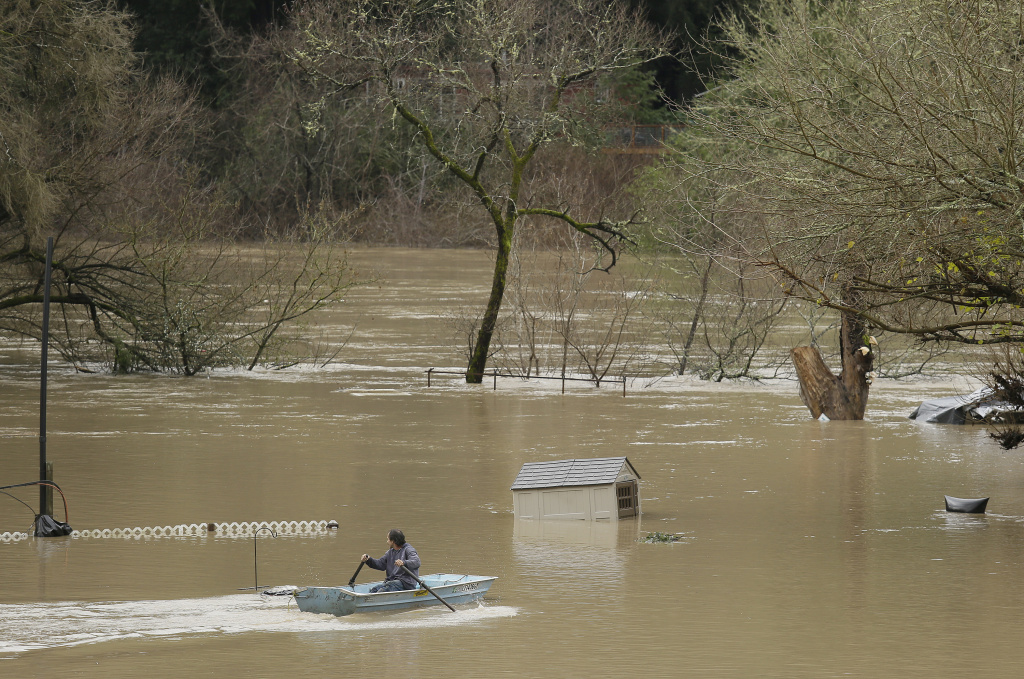 A man uses a rowboat to make his way through a flooded RV park as the Russian River flows in the distance on Jan. 9, 2017, near Forestville, Calif. A massive storm system stretching from California into Nevada lifted rivers out of their banks, flooded vineyards and forced people to evacuate after warnings that hillsides parched by wildfires could give way to mudslides.