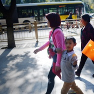 A woman and a child holding up a miniature national flag walk along a road in Beijing on October 31, 2015.