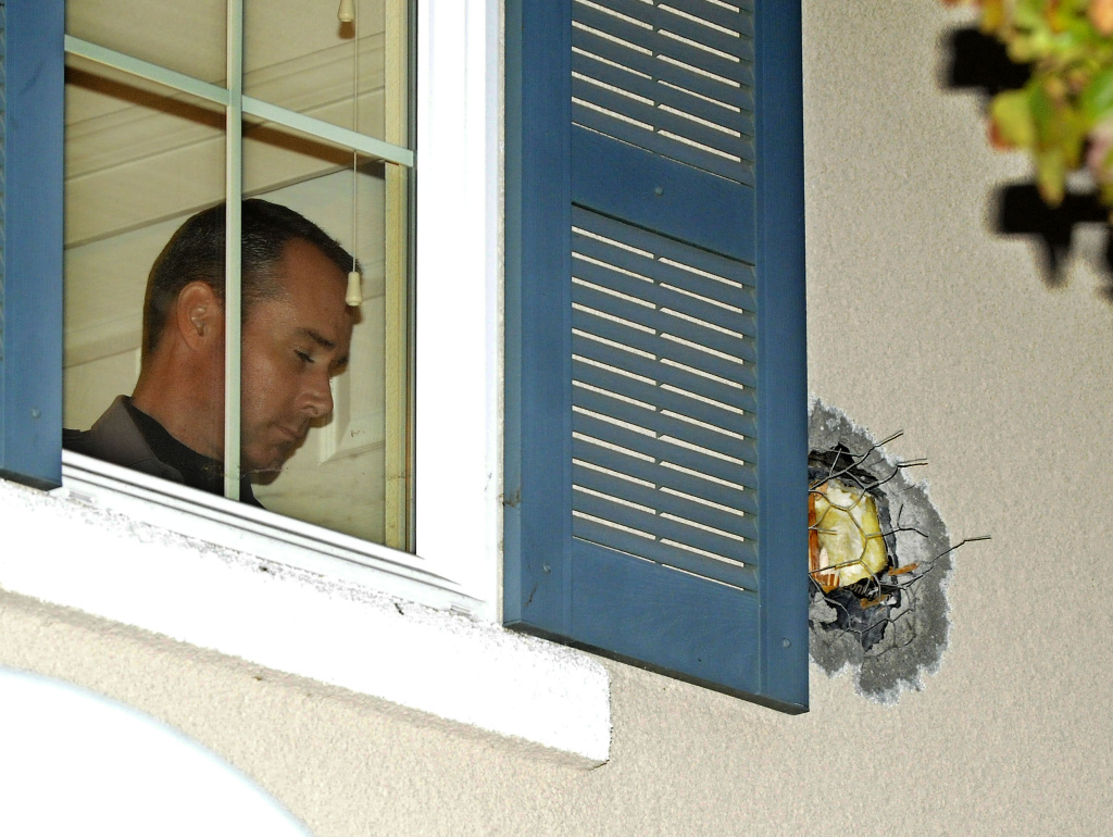 "A Dublin Police officer stands near the exit hole of a cannonball in the second story wall after it traveled through the California home on Tuesday. The cannonball was misfired during the taping of an episode of the Discovery Channel show ""MythBusters"" at the Alameda County Bomb Disposal Range."